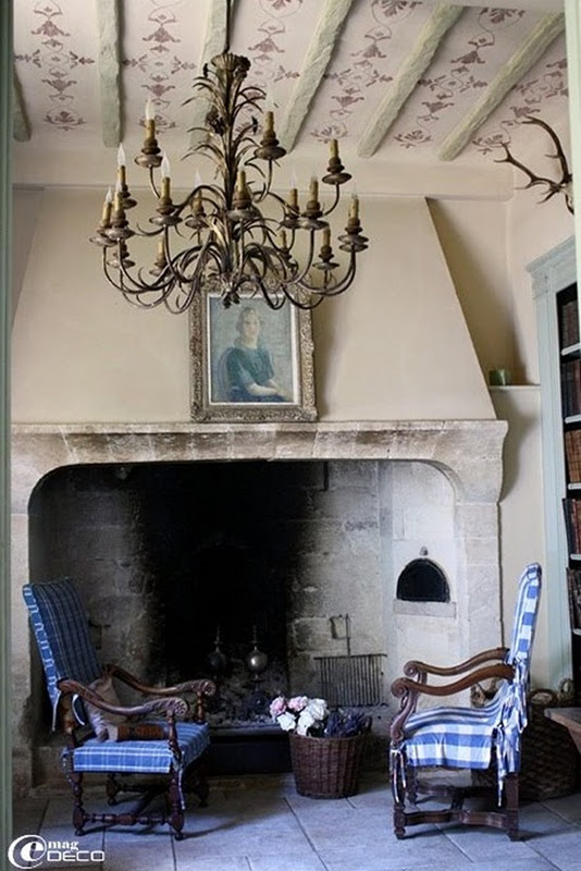 Beautiful stone walls and fireplace as a backdrop to the simple blue and white chairs