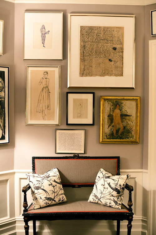 grey walls and fabric bench- but the genius is adding that orange trim and the mix of the art-Kate Spade Foyer