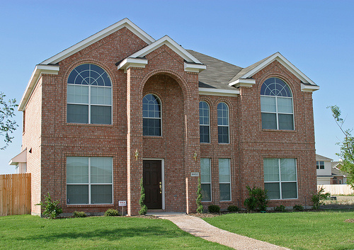 typical oversized home with lack of texture and details on brick, window trim, over-sized windows, and badly proportioned entry.