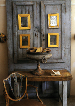 """Gilded frames on an antique paneled wall, along with a """"fancy"""" chair next to a rustic table...all natural surfaces with wear and tear."""